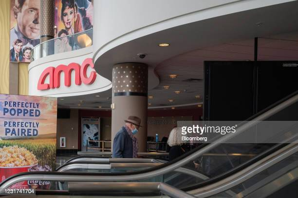People wearing protective masks ride an escalator at the AMC movie theater at the Westfield Century City shopping mall in Los Angeles, California,...