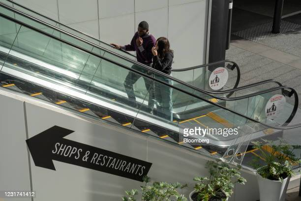People wearing protective masks ride an escalator at the Westfield Century City shopping mall in Los Angeles, California, U.S. On Monday, March 15,...