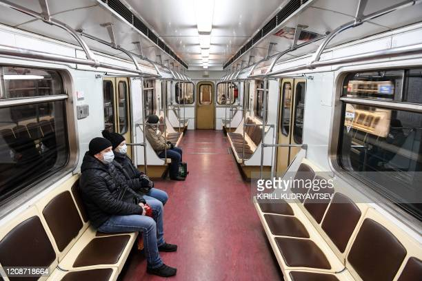 People wearing protective masks seat in a Moscow subway car in Moscow on March 31 amid the spread of the COVID-19 coronavirus. - The mayor of Moscow...