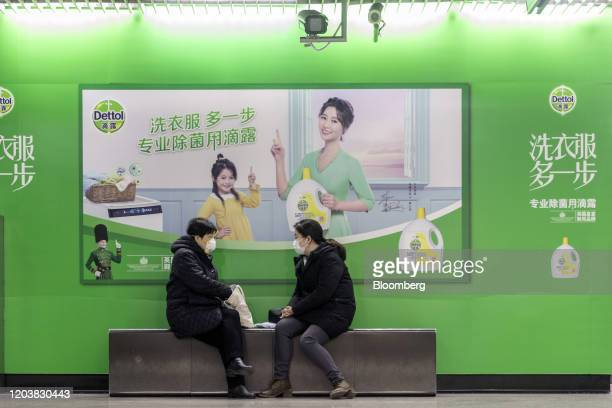 People wearing protective masks sit in front of an advertisement for Reckitt Benckiser Group Plc's Dettol laundry detergent at a subway station in...