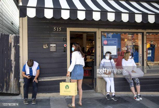 People wearing protective masks sit outside a North Face store on Main Street in Park City Utah US on Saturday Aug 1 2020 From California's wine...