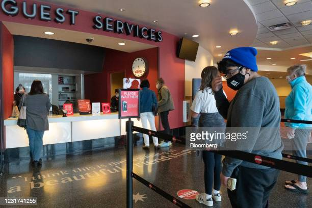 People wearing protective masks stand in line to buy tickets at the AMC movie theater at the Westfield Century City shopping mall in Los Angeles,...