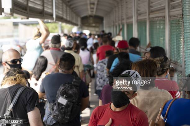 People wearing protective masks stand in line to enter the U.S. At a border crossing in Matamoros, Mexico, on Wednesday, May 6, 2020. A new 20-bed...