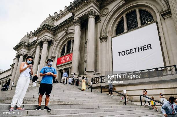 People wearing protective masks stand on the steps as visitors wait in line during the public reopening at the Metropolitan Museum of Art in New...