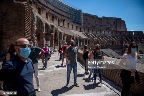 People wearing protective masks visit the Coliseum monument after three months of closure due to the Coronavirus pandemic during phase two of the...