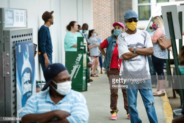 People wearing protective masks wait in line for free hand sanitizer outside a supermarket in the Fondren District of Jackson, Mississippi, U.S., on...