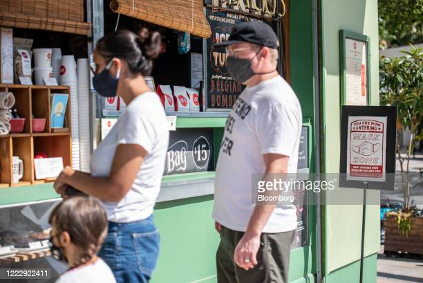 People wearing protective masks wait in line outside a coffee shop in Austin, Texas, U.S., on Thursday, June 25, 2020. Texas reported a record 5,489...