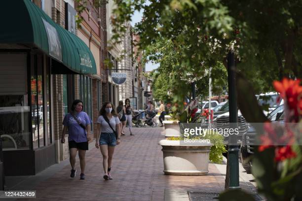 People wearing protective masks walk down Poyntz Avenue in downtown Manhattan, Kansas, U.S., on Thursday, July 2, 2020. Kansas' top public health...