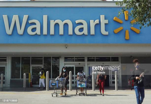 People wearing protective masks walk from a Walmart store on May 18, 2021 in Hallandale Beach, Florida. Walmart announced that customers who are...