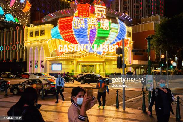 People wearing protective masks walk in front of the Casino Lisboa, operated by SJM Holdings Ltd., at night in Macau, China, on Tuesday, March 3,...