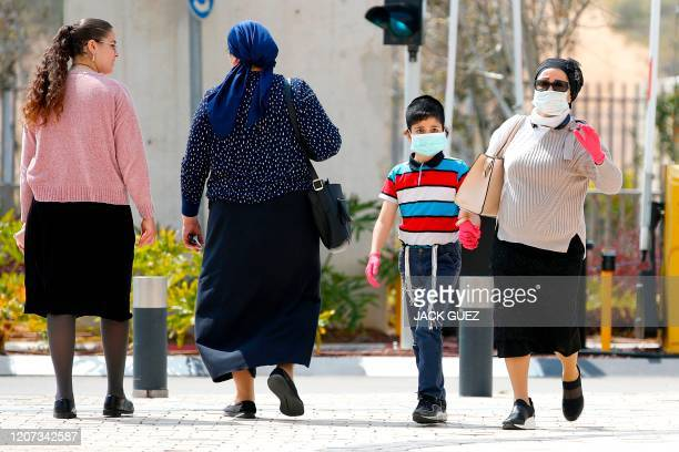 People wearing protective masks walk into Samson Assuta Ashdod University Hospital on March 16, 2020 in the southern Israeli city of Ashdod, as the...