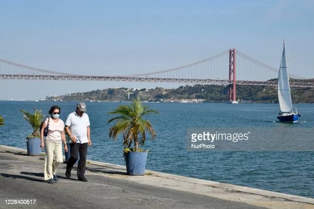 People wearing protective masks walk near the area of Doca do Bom Sucesso , Lisbon, on September 08, 2020. Portugal could receive up to six different...