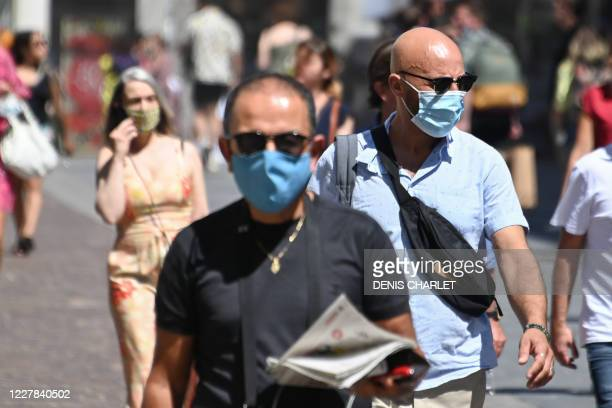 People wearing protective masks walk on a street in Lille, northern France, on July 30 as The Nord Prefecture announced, the reinforcement of the...