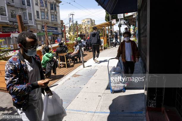 People wearing protective masks walk on Columbus Avenue in San Francisco, California, U.S., on Thursday, May 6, 2021. San Francisco advanced into the...