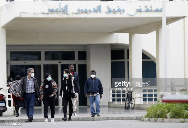 People wearing protective masks walk out of the Rafik Hariri University Hospital in the southern outskirts of the Lebanese capital Beirut on February...