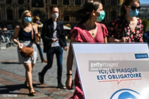 """People wearing protective masks walk past a sign reading """"Here, a protective mask is compulsory"""" on a street in Lille, northern France, on July 30 as..."""