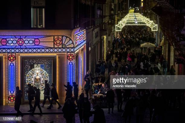 People wearing protective masks walk past Christmas decorations and buy gifts at Via dei Condotti, during the restrictions to contain the spread of...