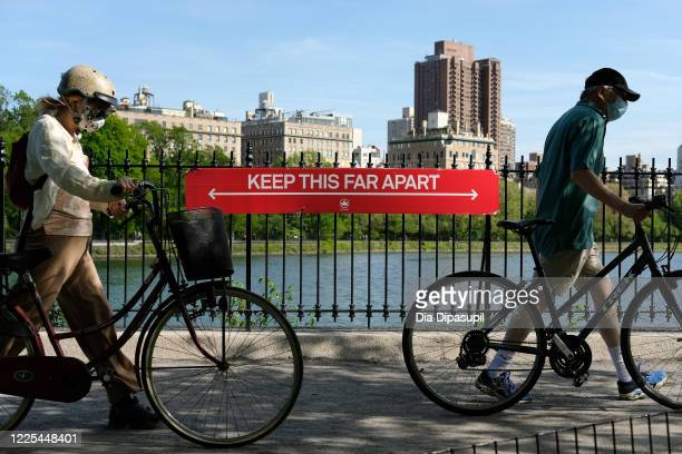 People wearing protective masks walk their bicycles past a social distancing sign reading KEEP THIS FAR APART at Jacqueline Kennedy Onassis Reservoir...