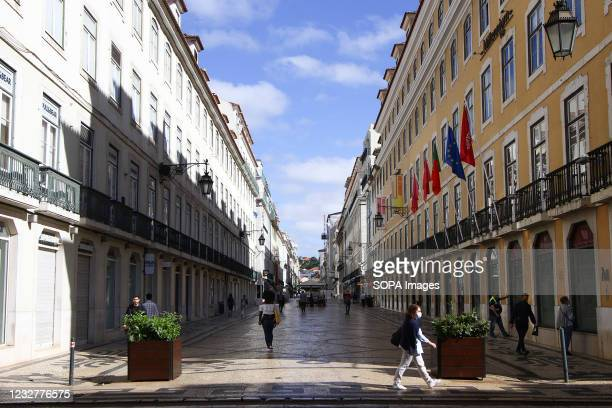 People wearing protective masks walk through Baixa district, Lisbon. According to data provided by the General Health Direction , Portugal is...