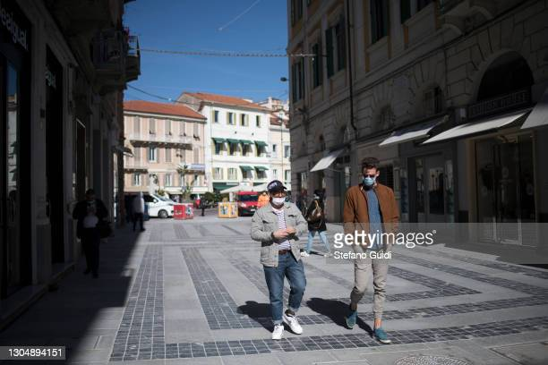 People wearing protective masks walk through the city on March 02, 2021 in Sanremo, Italy. The 71th Sanremo Music Festival 2021 starts today in the...