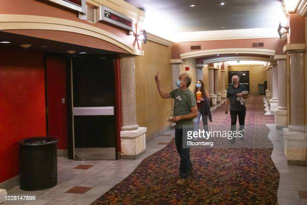 People wearing protective masks walk towards a theater at a Regal Cinemas theater in Austin, Texas, U.S., on Friday, Aug. 21, 2020. Regal Cinemas is...