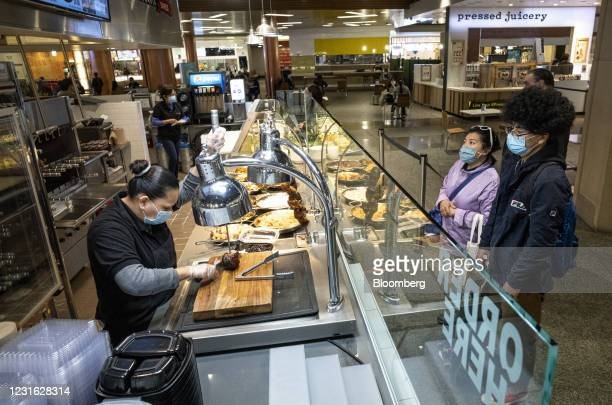 People wearing protective masks watch as a server cuts meat at the food court inside the Westfield San Francisco Centre shopping mall in San...