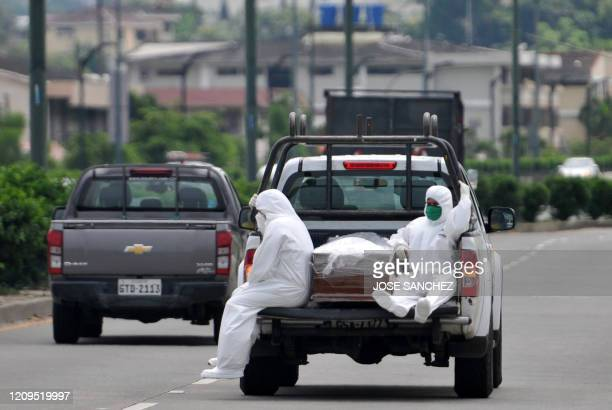TOPSHOT People wearing protective suits accompany a coffin on a truck near Los Ceibos hospital in Guayaquil Ecuador on April 8 amid the new...