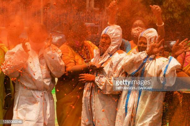 People wearing protective suits as a preventive measure against the spread of the Covid-19 coronavirus, play with coloured powders as they celebrate...