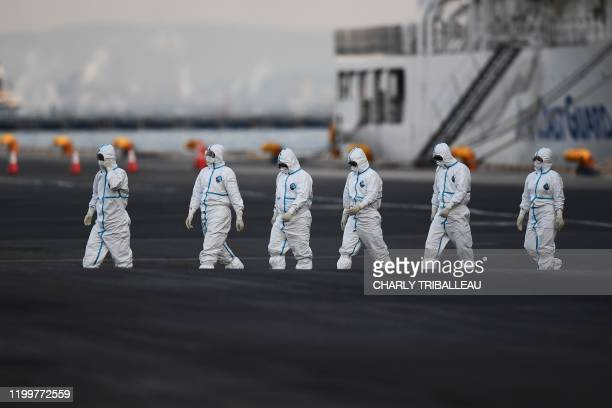 TOPSHOT People wearing protective suits walk from the Diamond Princess cruise ship with around 3600 people quarantined onboard due to fears of the...