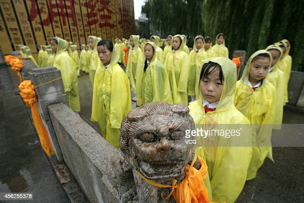 People wearing raincoats participate in 2014 Confucius Memorial Ceremony on September 28 2014 in Jining Shangdong province of China Memorial ceremony...