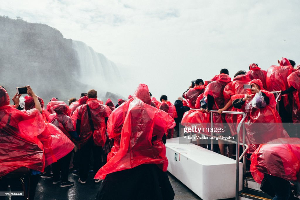 People Wearing Red Raincoat Against Waterfall : Stock Photo
