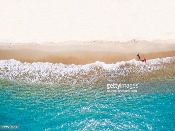 people wearing red shirts walking footprints on the beach white with blue sea waves , aerial view . - riva dell'acqua foto e immagini stock