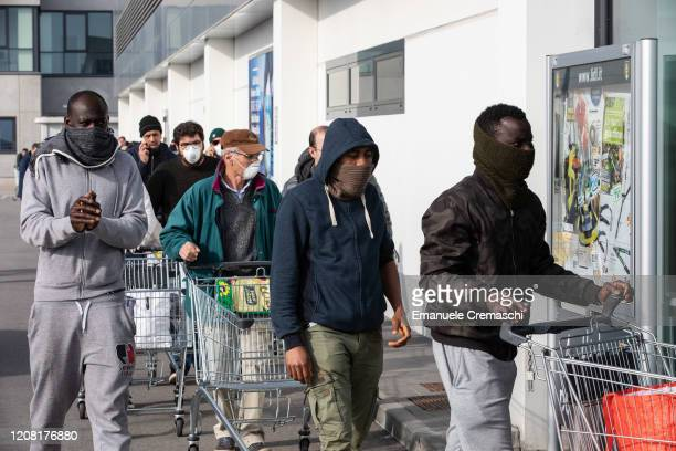 People wearing respiratory masks wait to be given a 10minutes access to shop in a LIDL supermarket in groups of twenty people on February 23 2020 in...