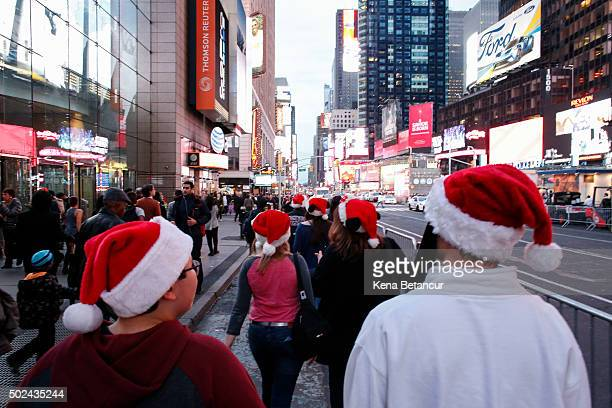 People wearing Santa Claus hats walk in Times Square on December 24 2015 in New York City Lastminute shoppers get some of the best deals many of the...