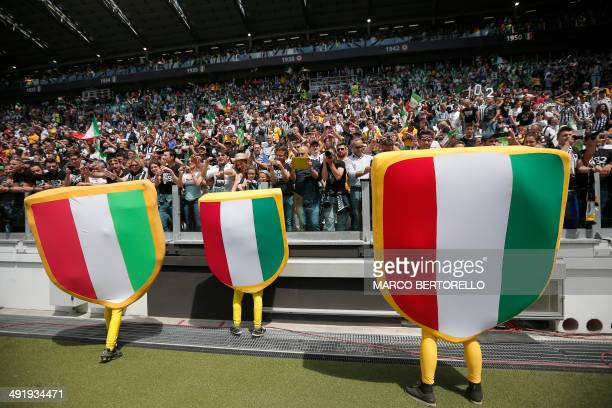 People wearing 'Scudetto' outfits cheer with fans before the Italian Serie A football match Juventus vs Cagliari on May 18 2014 at the Juventus...