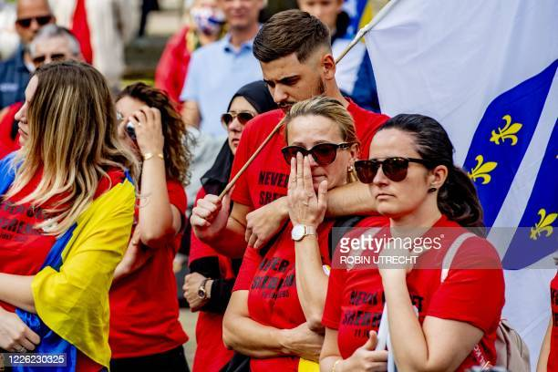 """People wearing shirts reading """"Never forget Srebrenica"""" attend the National commemoration of the Srebrenica Genocide on Het Plein in The Hague, on..."""