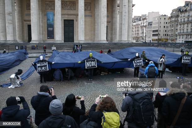 People wearing signs reading Tax Evasion the Notre Dame des Landes airport World Bank take part in a demonstration called by NGO's outside the...