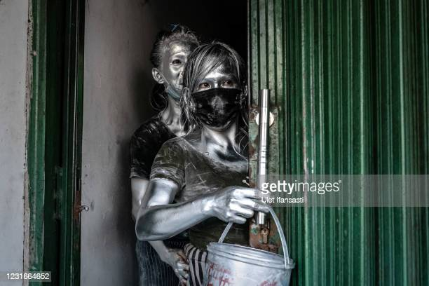 People wearing silver paint hide from civil service police as they begs on the street on March 11, 2021 in Depok, Indonesia. 'Silver Men', called...