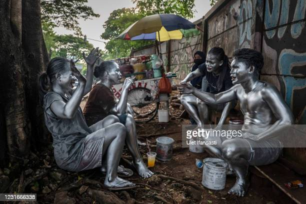 """People wearing silver paint take a rest as they beg on the street on March 10, 2021 in Depok, Indonesia. 'Silver Men', called """"Manusia Silver"""" in..."""