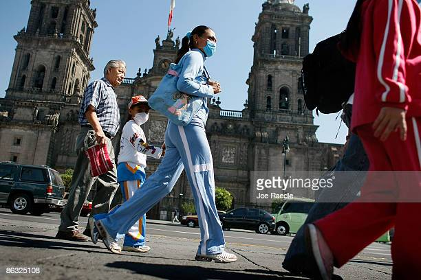People wearing surgical masks to help prevent contamination with swine flu walk past the Mexico City Cathedral on May 1 2009 in Mexico City Mexico...