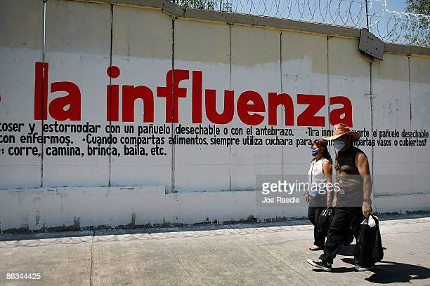 People wearing surgical masks to help prevent contamination with swine flu walk past a sign warning of the influenza on May 1 2009 in Mexico City...