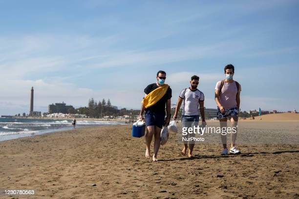 People wearing surgical masks walk on the beach of Maspalomas on the island of Gran Canaria, Spain on January 23, 2021.