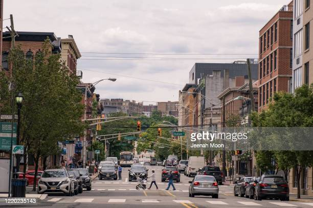 People wearing the protective mask walk on the street as the city reopens from the coronavirus lockdown on June 15, 2020 in Hoboken, New Jersey. The...