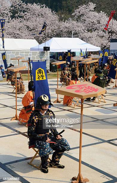 People wearing traditional armor and kimono act as peice of the Shogi or Japanese chess during the 'Ningen Shogi' at Mt Maizuru of the Tendo Park on...