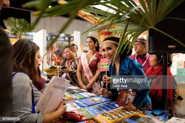 People wearing traditional Balinese costume speak to guests at the Bali tourism board stand at the World Travel Market event at the ExCel centre on...