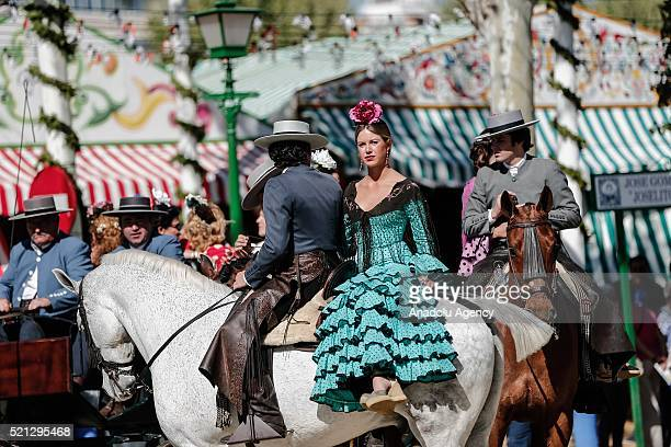 People wearing traditional dressses are seen during horseback parade at the 'Feria de Abril 2016' the traditional Seville's Fair with 169 years of...