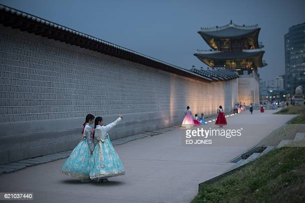 TOPSHOT People wearing traditional Korean hanbok dress pose for photos as they visit Gyeongbokgung palace in central Seoul on November 4 2016 / AFP /...