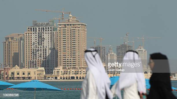 People wearing traditional Qatari clothing walk along a beachfront opposite new highrise buildings under construction on the manmade peninsula called...