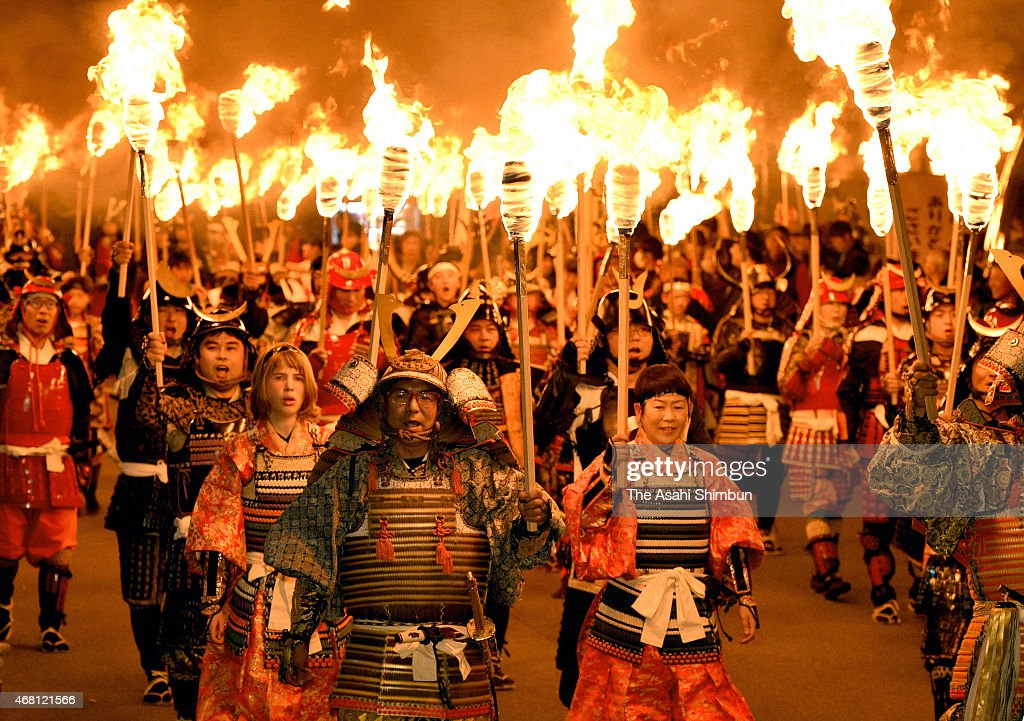 People wearing traditional samurai worrior armours march on with holding flaming torches during the 'Kan-o-kaen', or cherry blossom viewing fire festival, on March 28, 2015 in Unzen, Nagasaki, Japan.