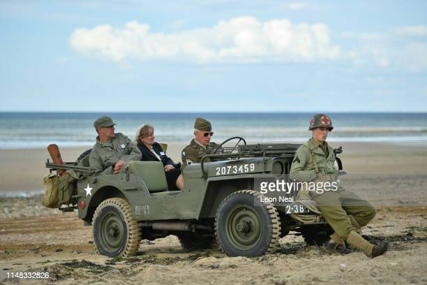 People wearing vintage-style military costumes sit in a US military Willy's Jeep at a D-Day 75th Anniversary event on Juno beach on June 6, 2019 in...